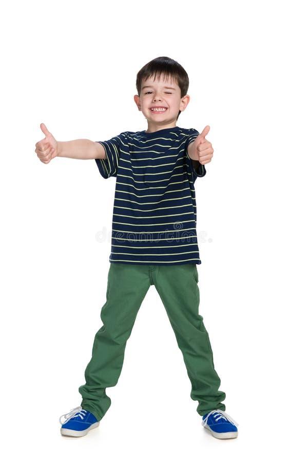 Junge in grüne Hose hält seine Daumen hoch lizenzfreies stockfoto