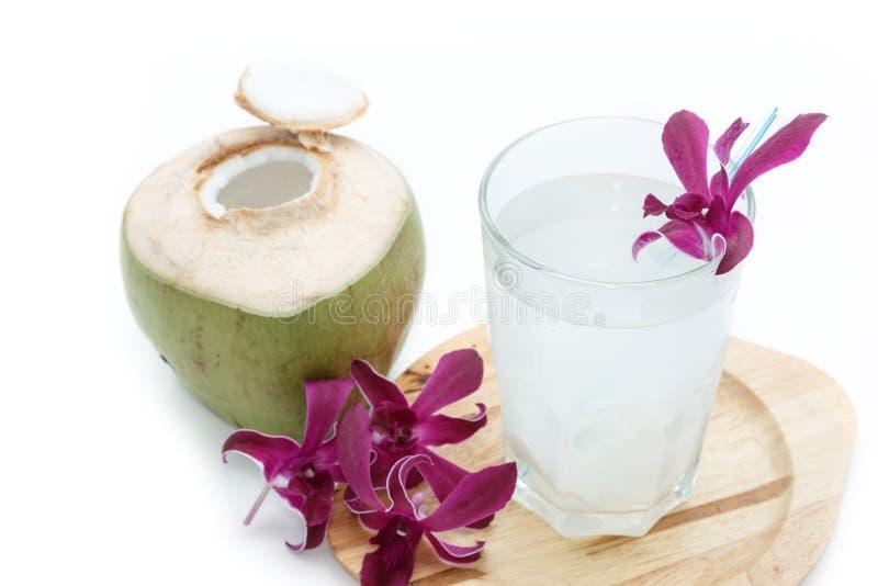 Junge grüne Kokosnuss mit Trinkhalm und Orchidee lizenzfreie stockfotos