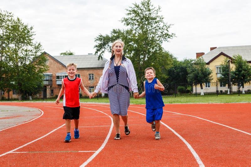 Junge Großmutter lässt ein Sportstadion mit den Grandkids laufen stockfotos