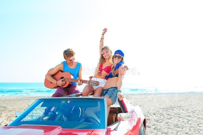 Junge Gruppe, die Spaß auf dem Strand spielt Gitarre hat lizenzfreies stockfoto