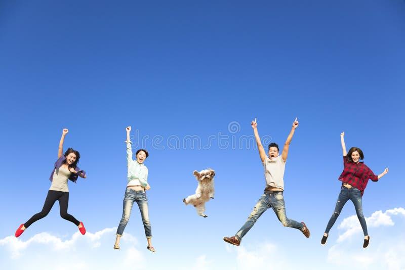 junge Gruppe, die zusammen mit Hund springt stockbilder