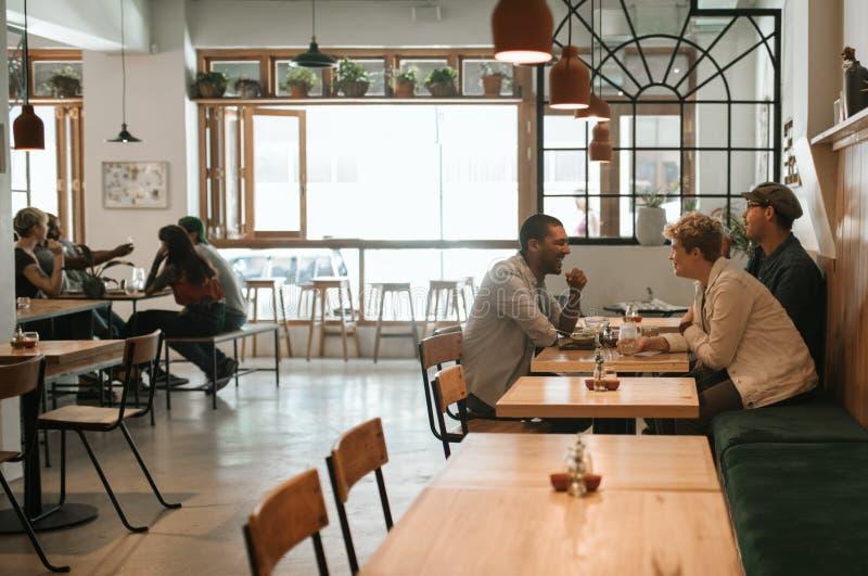 Junge Gruppe Freunde, die zusammen in einer Bistro zu Mittag essen lizenzfreie stockfotografie