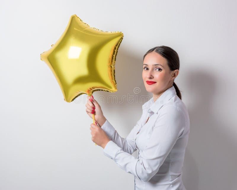 Junge hübsche Frau, die einen sternförmigen Ballon hält Glücklicher Mann genießt an den Feiertagen in dem Meer stockbild