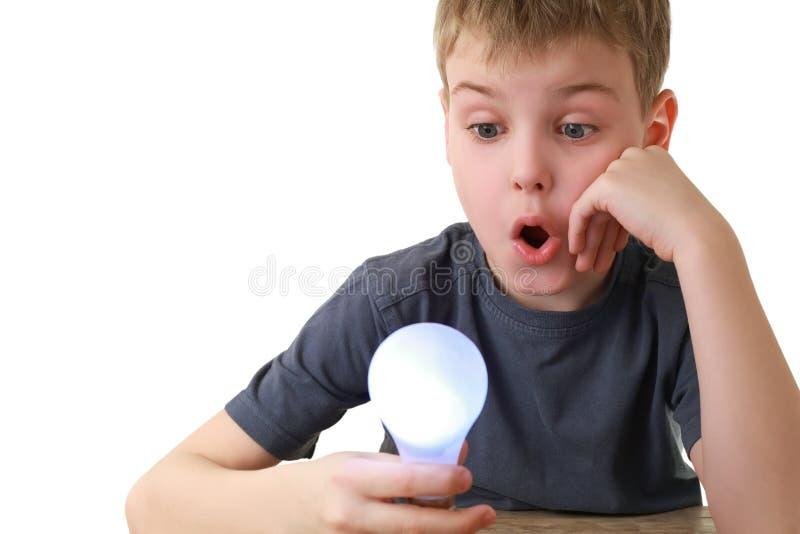 Junge hält anschließen Lampe und Blicke an ihr an lizenzfreie stockfotografie