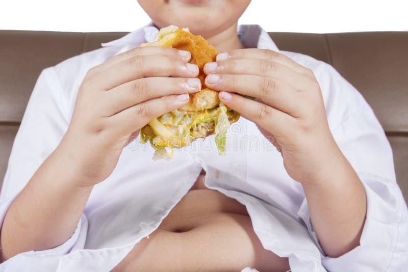 Junge hält einen Cheeseburger stockfotografie