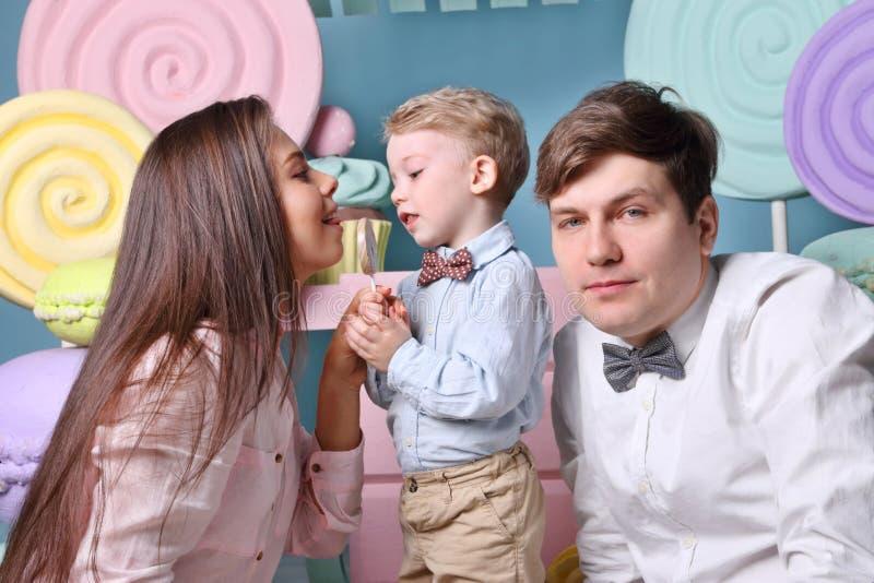 Junge hält Lutscher, leckt Mutter ihn und Vater stockfotos