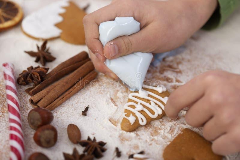 Junge Hände schmücken Lebkuchen mit weißer Vereisung lizenzfreies stockfoto