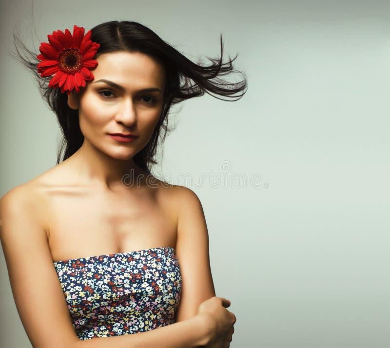 Junge hübsche Brunettefrau mit roter Blume im Fliegenhaar, Leben stockfotos