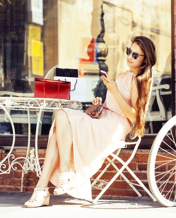 Junge hübsche Brunettefrau nach dem Einkaufsc$sitzen am Café draußen auf dem Straßenlächeln stockfoto