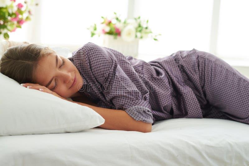 Junge hübsche Dame in den Pyjamas, liegend auf Bett mit dem weißen Bedsheet lizenzfreie stockbilder