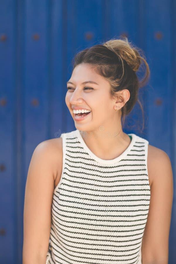 Junge hübsche Frau auf dem blauen Hintergrund, der weg lachend schaut stockbild