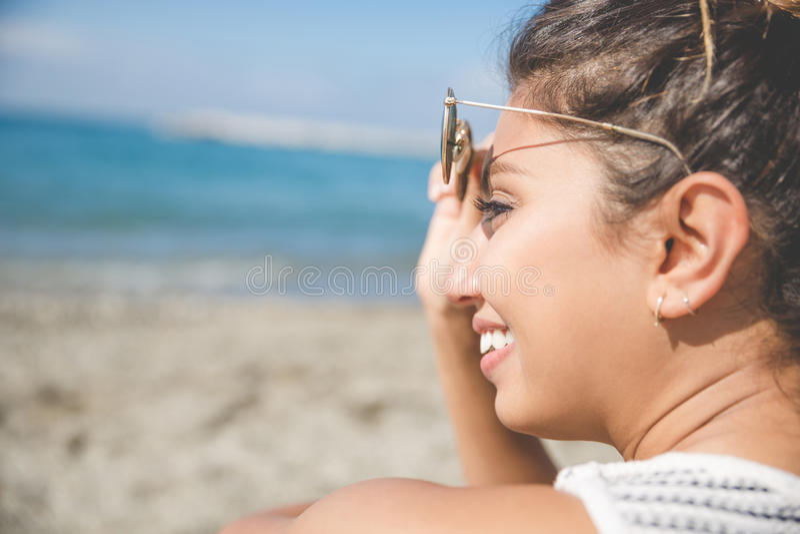 Junge hübsche Frau auf dem Strand, der das Sonnenbrillelächeln hält lizenzfreies stockbild