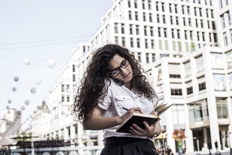 Junge hübsche Frau in der Büroartkleidung machen Anmerkungen in ihrem Notizbuch und die Unterhaltung am Telefon mit jemand stockfotos