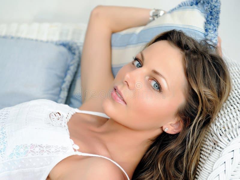 Junge hübsche Frau, die auf einem Sofa im Haus sich entspannt lizenzfreie stockbilder