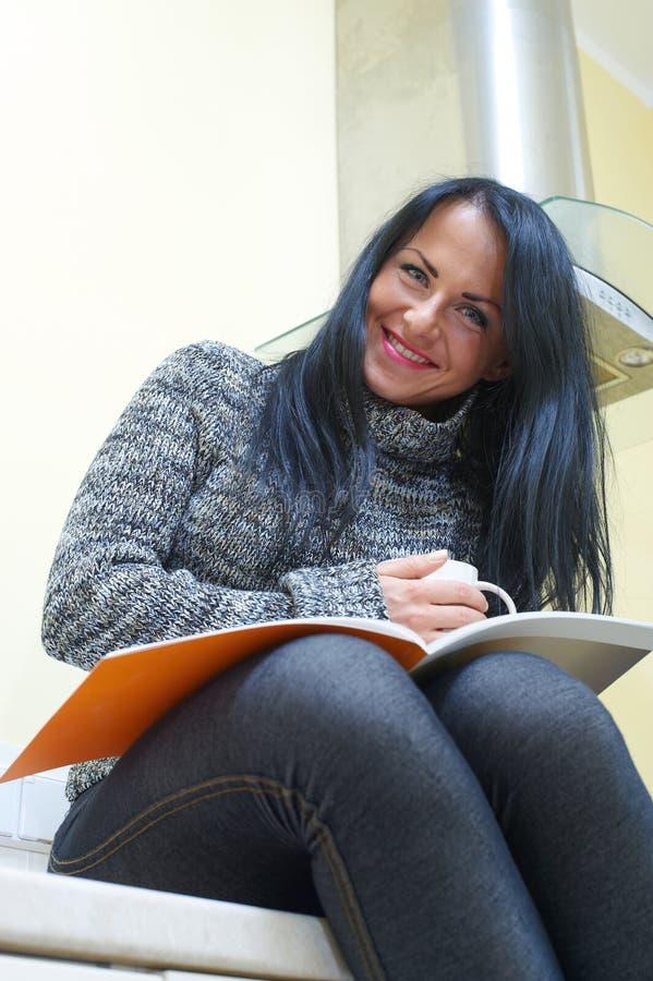 Junge hübsche Frau, die auf einer Tabelle sitzt stockfotografie
