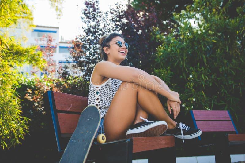 Junge hübsche Frau, die auf Strand mit dem Skateboardlachen sitzt lizenzfreie stockfotos