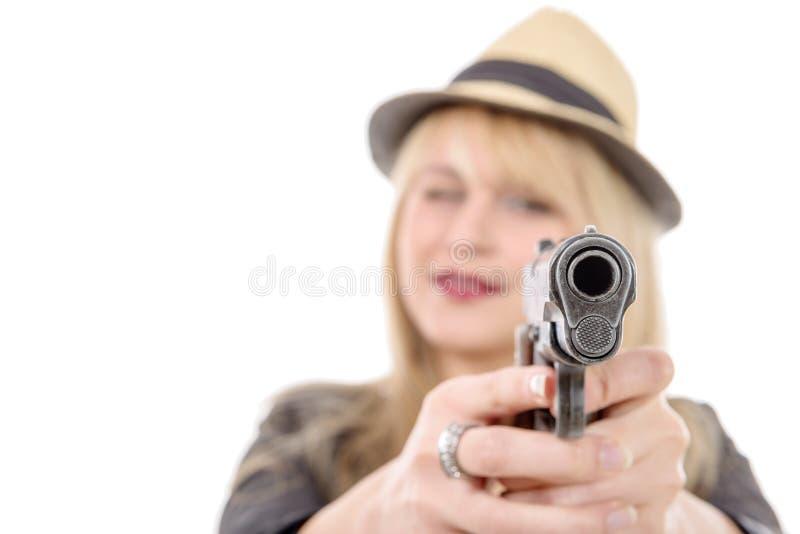 Junge hübsche Frau, die ein Gewehr auf die Kamera mit einer Hand zeigt, lizenzfreie stockbilder