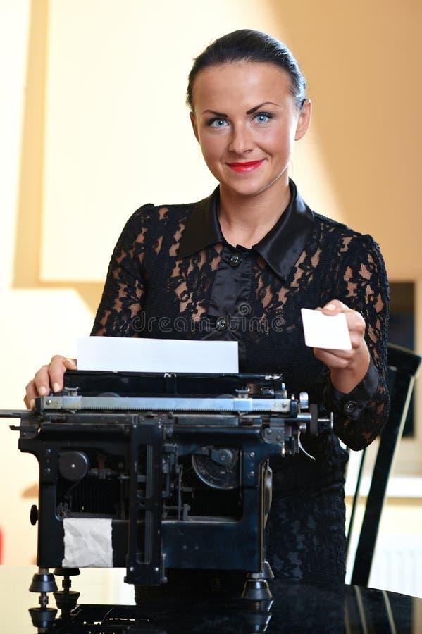 Junge hübsche Frau, die an einer Schreibmaschine sitzt stockfotografie