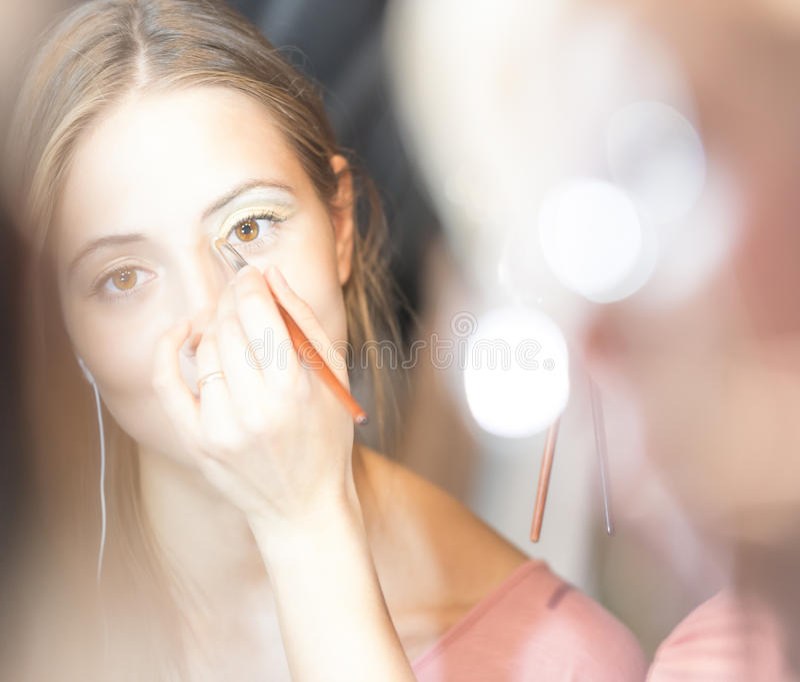 Junge hübsche Frau, die Make-up mit Pinsel erhält. lizenzfreies stockbild
