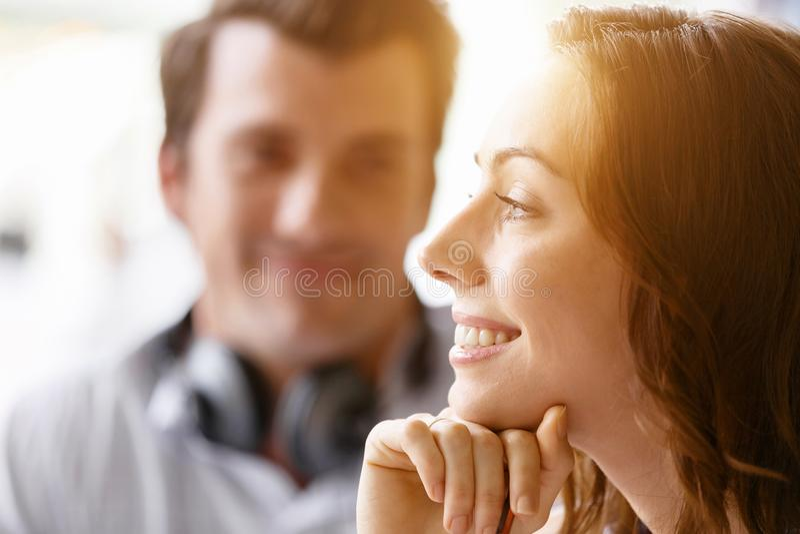 Junge hübsche Frau, die mit Mann auf Hintergrund lächelt stockfoto
