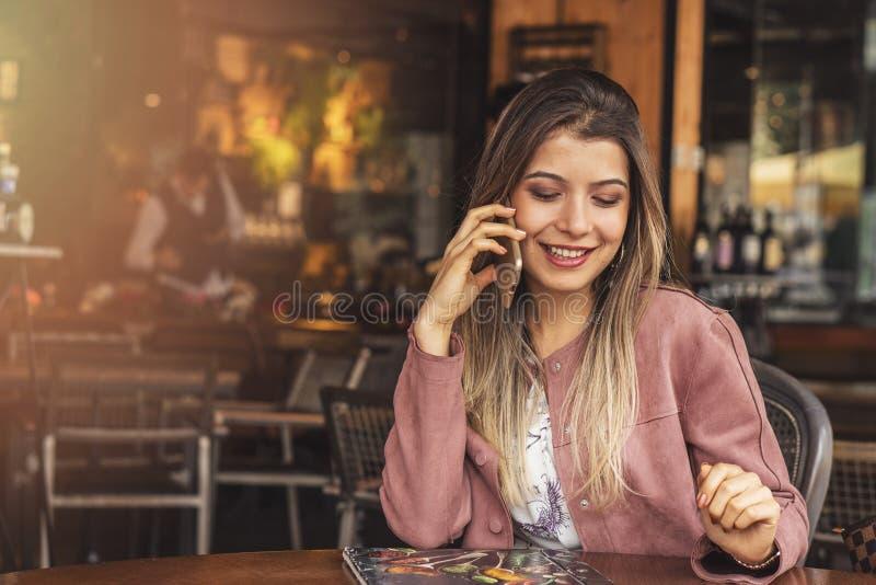 Junge hübsche Frau, die mit Zelltelefon beim in der Kaffeestube während der Freizeit allein sitzen, attraktive Frau mit nettem ne lizenzfreie stockfotos