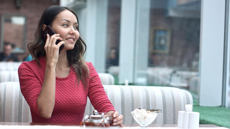Junge hübsche Frau, die mit Zelltelefon beim im Café allein sitzen nennt lizenzfreie stockbilder