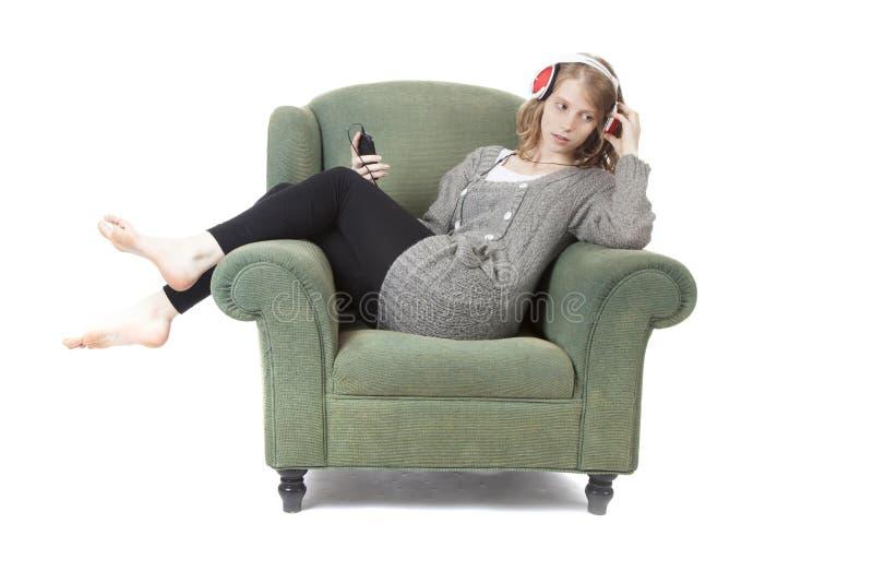 Junge hübsche Frau, die Musik im Lehnsessel hört lizenzfreie stockfotos