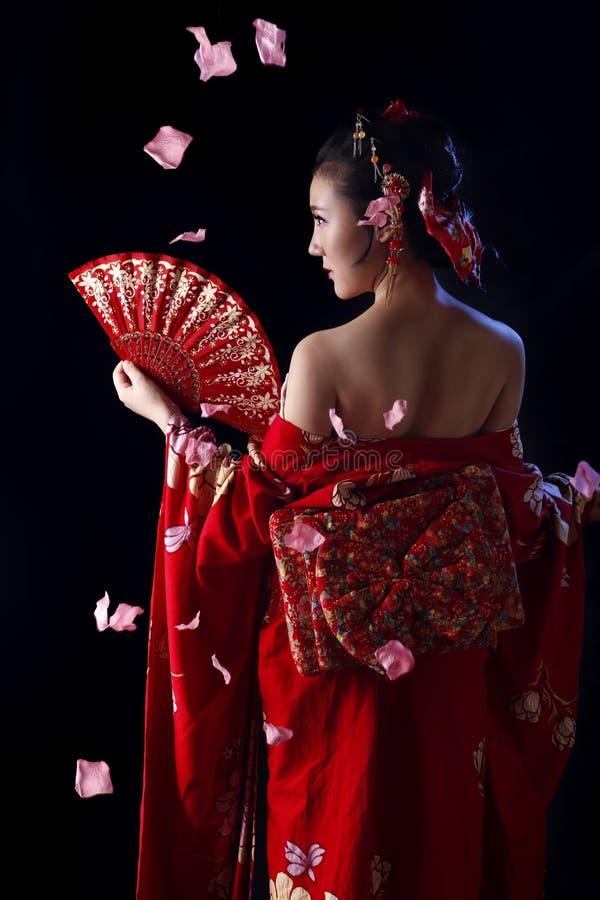 Junge hübsche Frau, die roten Kimono trägt lizenzfreies stockfoto