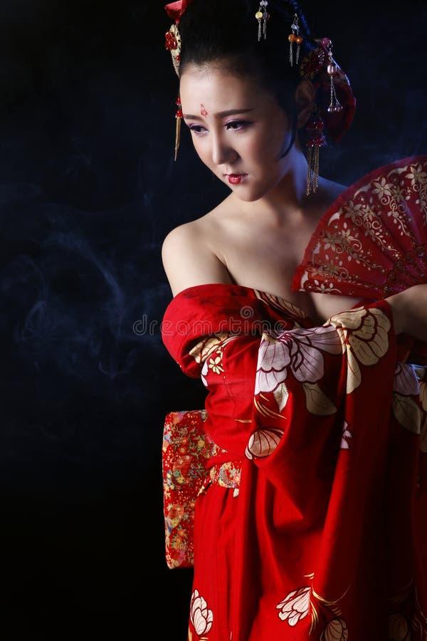 Junge hübsche Frau, die roten Kimono trägt lizenzfreie stockbilder