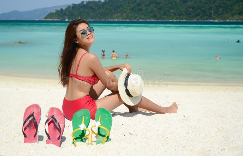 Junge hübsche Frau im roten Bikini, der am Türkisseestrand mit Frischluft des Sommers sich entspannt lizenzfreies stockbild