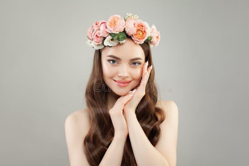 Junge hübsche Frau mit klarer Haut, gesundes Haar und Blumen winden stockfoto