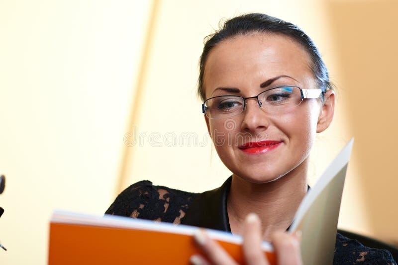 Junge hübsche Frau mit orange Buch in den Händen lizenzfreie stockfotos
