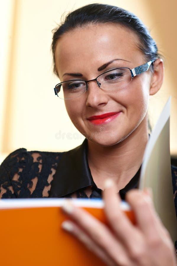 Junge hübsche Frau mit orange Buch in den Händen stockfotografie