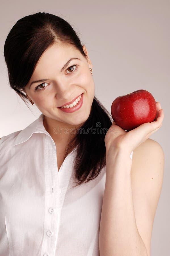 Junge hübsche Frau mit rotem Apfel lizenzfreie stockbilder