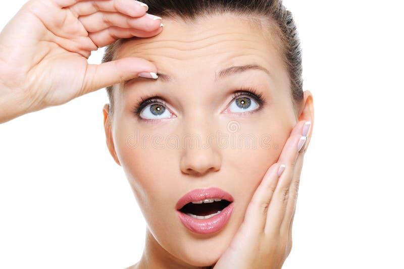 Junge hübsche Frauenpressunghaut auf Stirn stockbild