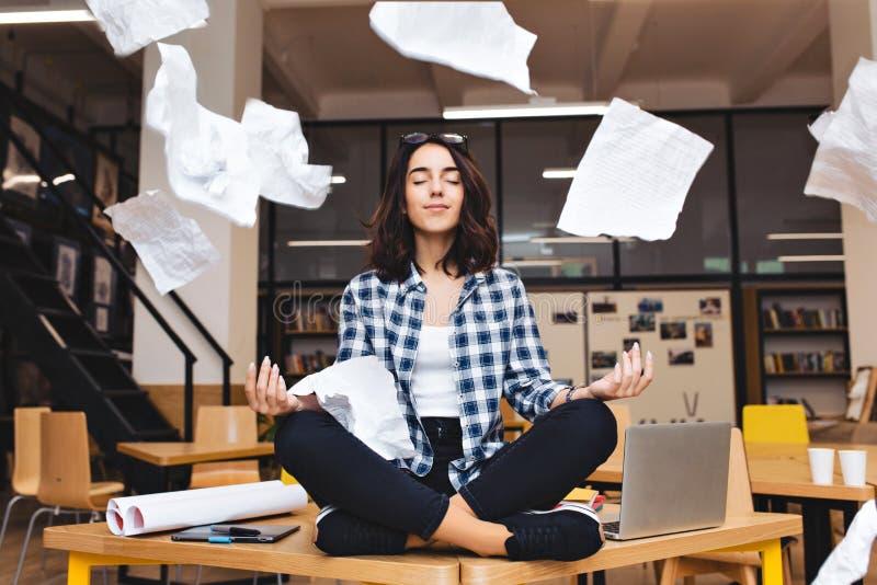 Junge hübsche frohe brunette Frau, die auf Tabelleneinfassungs-Arbeitsmaterial und fliegenden Papieren meditiert Frohe Stimmung,  stockbilder
