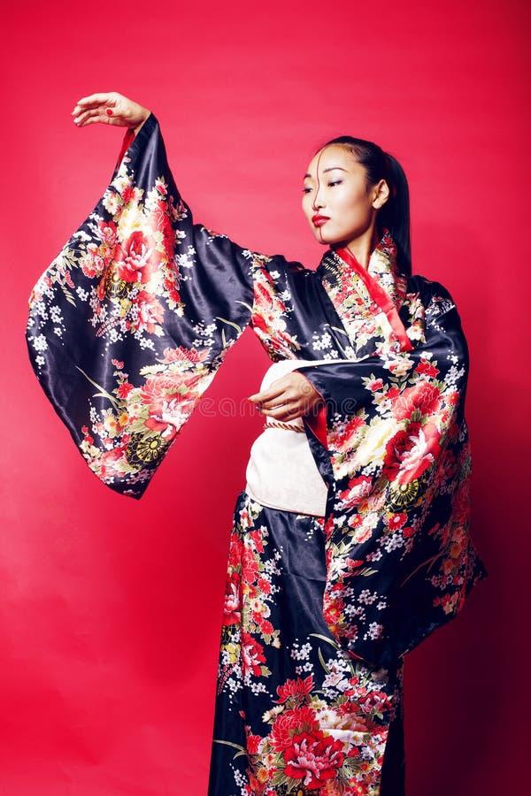 Junge hübsche Geisha auf dem roten Hintergrund, der im Kimono, orientalisches Leutekonzept aufwirft stockbild