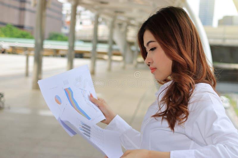 Junge hübsche Geschäftsfrau, die Diagramme und Diagramme in ihren Händen an allgemeinem im Freien analysiert stockfotos