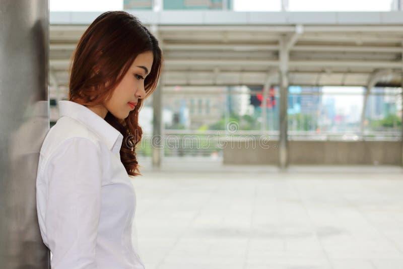 Junge hübsche Geschäftsfrau, die einen Pfosten lehnt und öffentlich etwas im Freien mit Kopienraumhintergrund denkt lizenzfreies stockbild