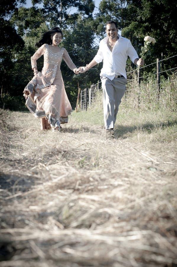 Junge hübsche indische lachende Paare, die in Feld mit weißen Rosen laufen lizenzfreie stockfotos