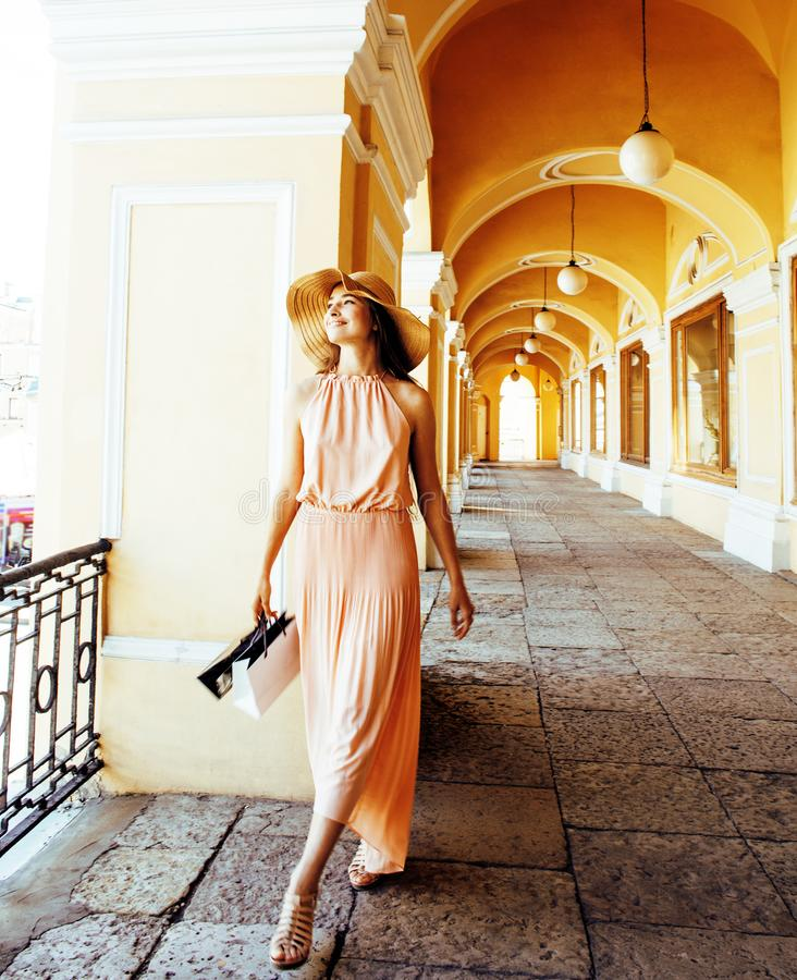 Junge hübsche lächelnde Frau im Hut mit Taschen auf dem Einkaufen am Speicher lizenzfreie stockfotografie