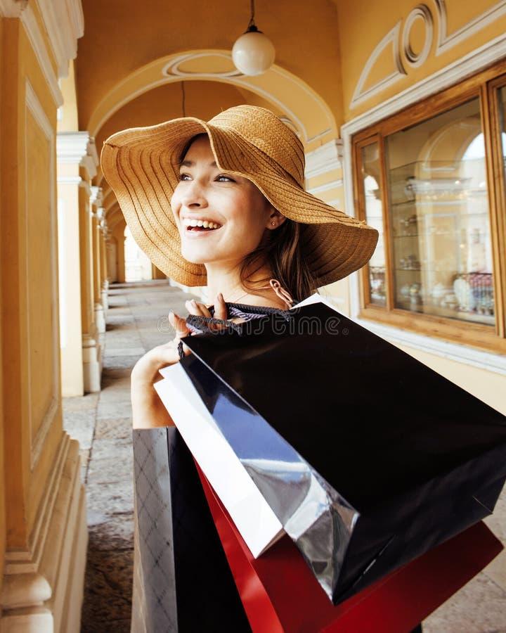 Junge hübsche lächelnde Frau im Hut mit Taschen auf dem Einkaufen am Speicher stockfotografie