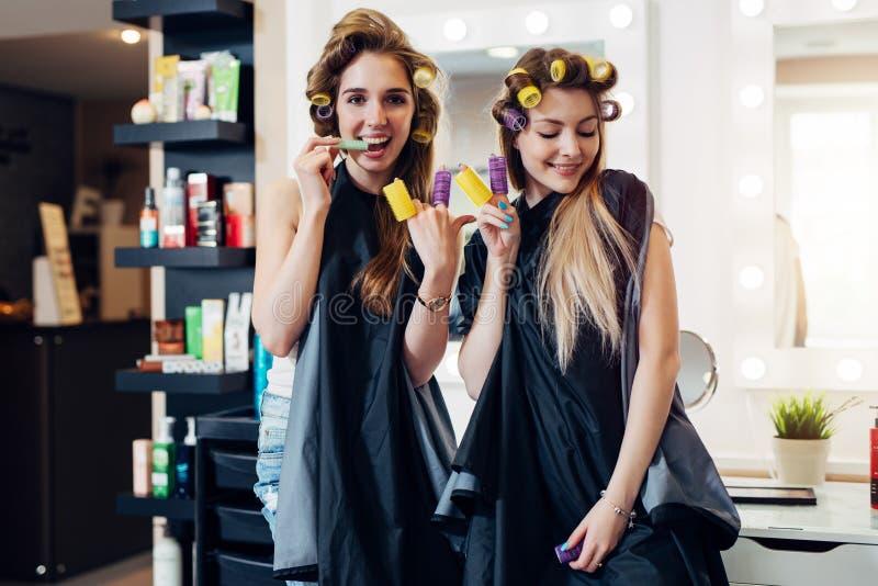 Junge hübsche Mädchen in den Kapen mit Haarlockenwicklern herum vermasselnd im Schönheitssalon Freundinnen, die Teufelhorn und -s stockfotografie