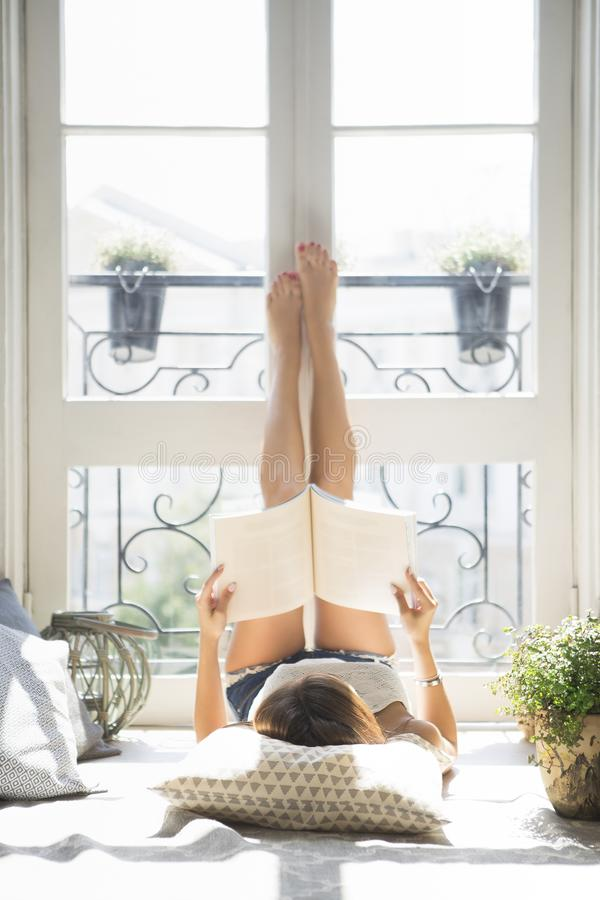 Junge hübsche Mädchenlesemodezeitschrift nahe Fenster stockbilder