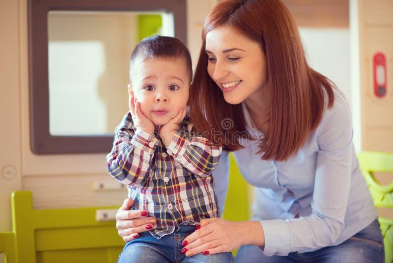 Junge hübsche Mutter, die mit ihrem Babysohn spielt und lacht lizenzfreies stockfoto