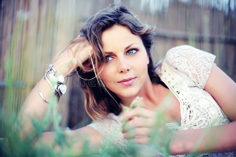 Junge hübsche Sommerfrau, die im Gras liegt stockbilder