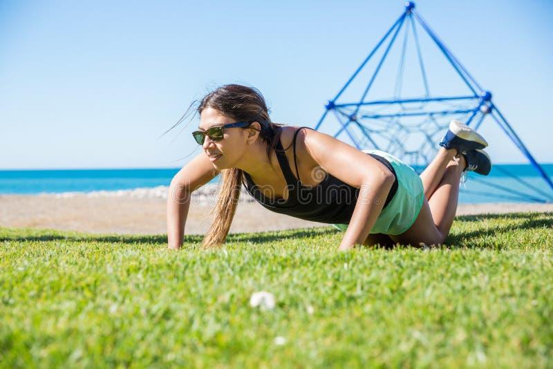 Junge hübsche Sportlerin, die draußen StoßUPS ausbildet stockfotografie