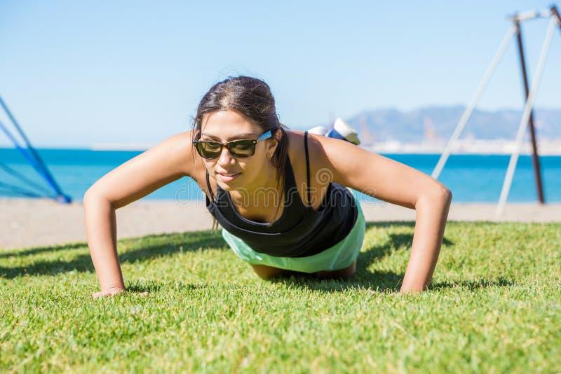 Junge hübsche Sportlerin, die StoßUPS auf Gras tut stockbilder