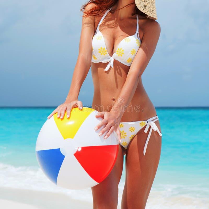 Junge h?bsche Frau mit Ball auf dem Strandhintergrund Gl?cklicher Lebensstil Wei?er Sand, blauer Himmel und Kristallmeer des trop lizenzfreie stockfotos
