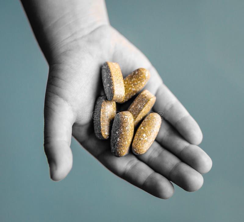 Junge h?lt Vitamine oder Verordnungspillen in der Palme der Hand Stellen Sie sch?tzende Schablone und die Pille gegen?ber, die im stockbilder